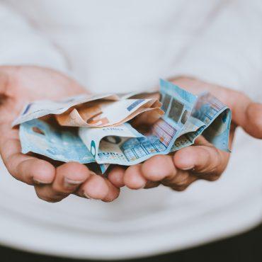 Hände halten Euro-Scheine. © Christian Dubovan on unsplash