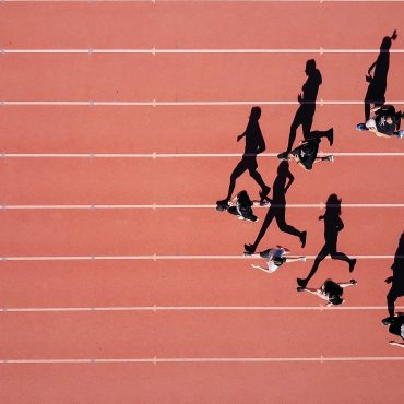 Schatten laufender Männer auf Tartanbahn